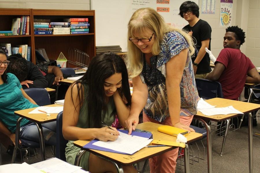 One of our new teachers, Ms. Nadeau, helps junior Korah McFarley with her math classwork.