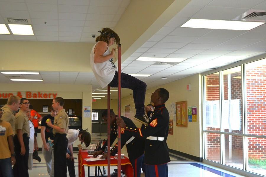 "Sophomore Chris Deters completes pullups at a Marine promotion in the cafeteria. The Marines present had set up a raised bar for students to perorm bar excerises for certain prizes. The rewards include a Marines car sticker, a Marines poster, a keychain, and a water bottle. For completing 21 pullups, Deters was awarded a water bottle proclaiming, ""Pain is weakness leaving the body."""