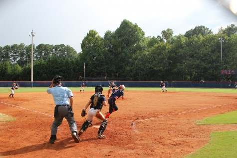 JV softball player Olivia Gomes (#7) runs to first after hitting a single.