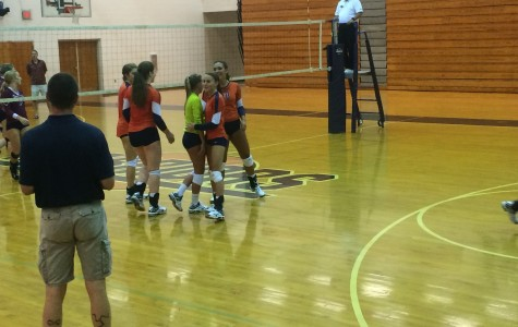 The Lady Warriors celebrate scoring a point as Coach Auld looks on.