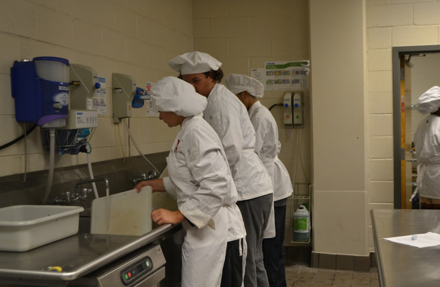 The NC culinary students wash up after cutting chicken as a project for their class.