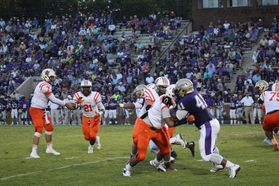 Quarterback Will Lovett (#7) handing off the ball to running back CJ Cole (#21) in the first quarter.