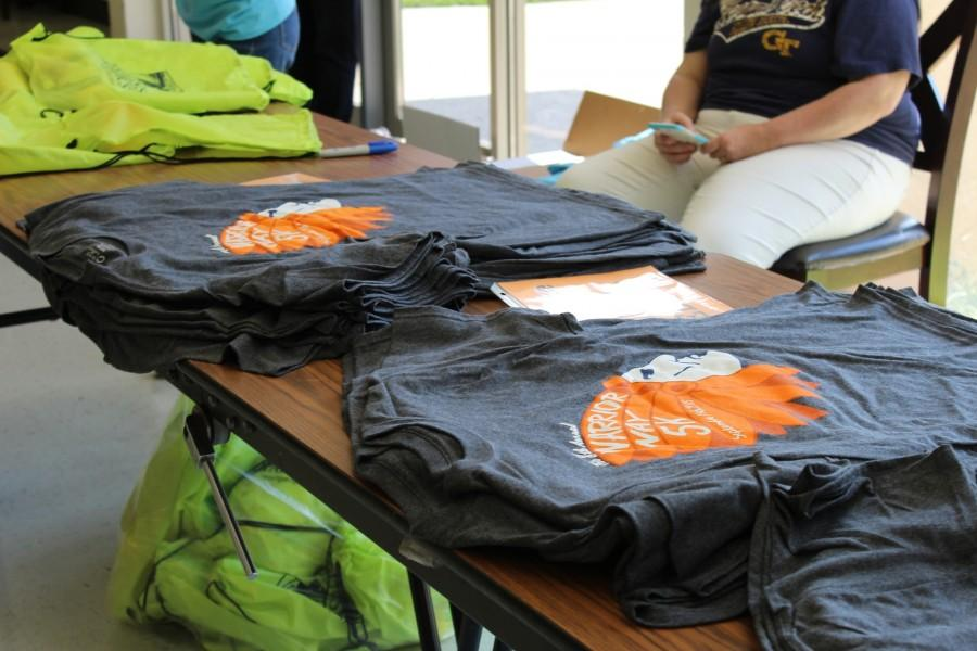 """NC Cross Country hands out shirts for those who signed up for the annual Warrior War 5K, taking place tomorrow, September 19. """"Warrior Way is our only fundraiser of the year and we hope to provide a great experience for all of our racers, we have about 350 signed up and we're going to use the NC trail, so it's fun to have it on campus and see the community and have family members and friends of our athletes come out to support them at what they do best,"""" said Cross Country coach Sarah Bowling. People wishing to participate in the race, but not yet signed up, can still sign up tomorrow by paying the 25 dollars in cash."""