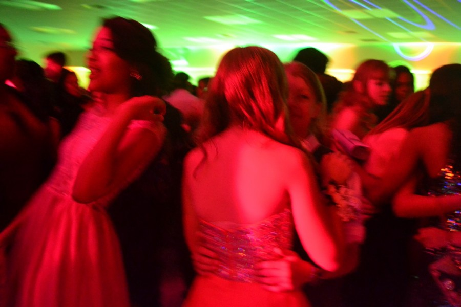 The Homecoming attendees are bathed in a red light as they dance to the music.