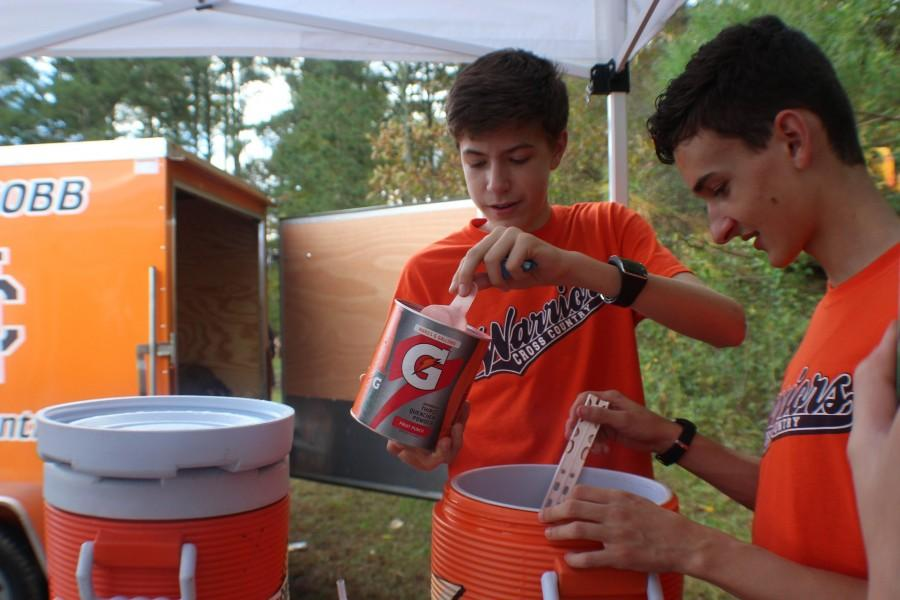 Sophomores Evan Morning and Marco Mancuso work together to prepare Gatorade for the race. Team members must set up tarps and tents and prepare food for each race.