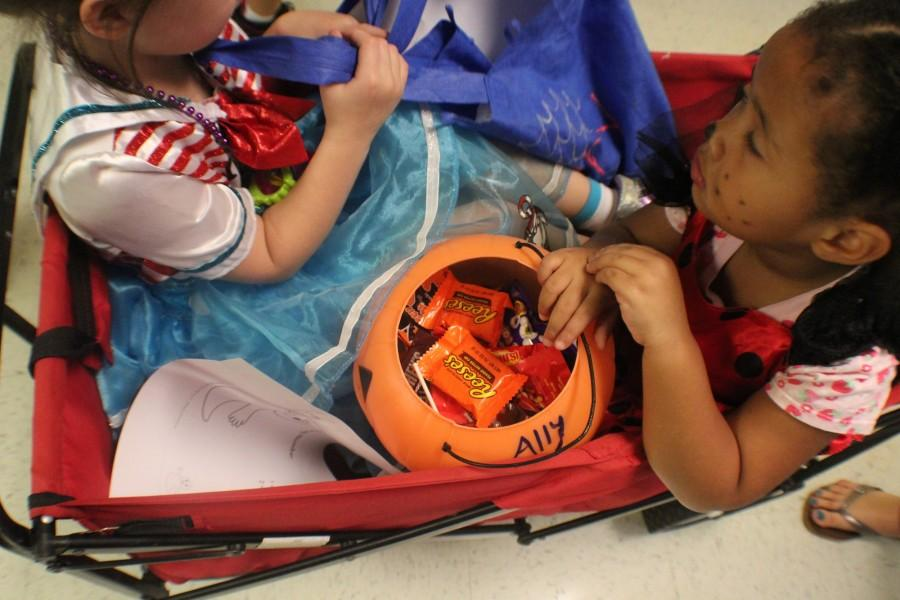 The kids received candy from many teachers. They seemed happy with all the candy and eagerly held their bags close.