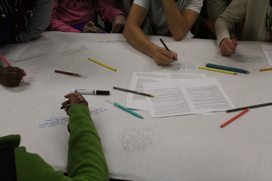 Students gather around large sheets of paper to read articles and discuss their opinions. There were also questions that went along with the articles and participants wrote their responses.