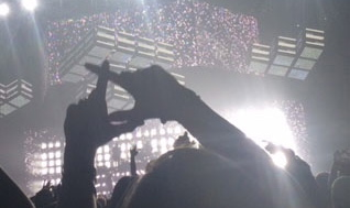 A fan holds up the XO symbol as the crowd begs for an encore, following the conclusion of the concert.