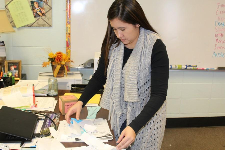 "New Spanish teacher Lorna Fair-Tham sorts papers while her students eat lunch. ""She makes sure everyone understands the work and that we understand what is expected of us,"" said junior Brittany Ent."