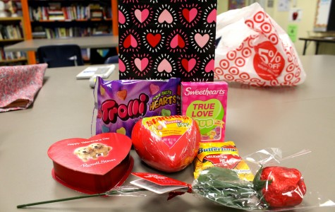 Anabel tries various Valentine's Day themed foods, including Russell Stover chocolate, Starburst Sweet and Sours, a chocolate rose, Butterfinger Valentine Hearts, Sour Sweethearts, and Trolli Sour Brite Hearts.