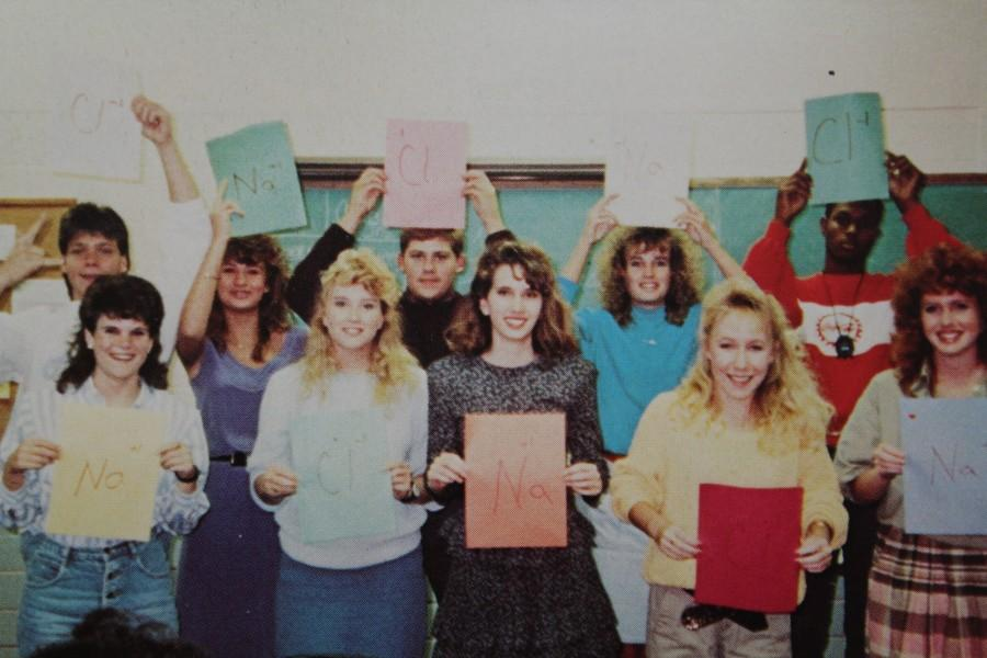 A NC chemistry class in 1988 displays what they have learned in class by holding up signs with the names of different elements on them.