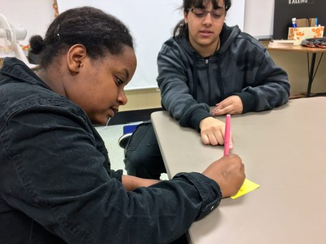 """Junior and Social Studies major Bethel Mamo works with Governor's Honors alumna, Fatima Elfakahany (Communicative Arts), to plan a list of items to bring to the camp. Mamo received her acceptance on March 25, 2016 and looks forward to the program. """"I want to learn more than I would be able to at school, like on topics I wouldn't get in normal classes. I am excited to be able to actually understand more content and know more in depth than I would regularly,"""" Mamo said."""