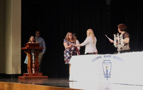 Junior Jessica Campbell receives her certificate and identification at the NHS Induction while junior Rebecca Cantrell signs her name in the NHS Induction book, awaiting her turn.