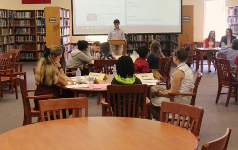 Middle schoolers work practice their skills in a mock conference setting, practicing public speaking and resolution writing skills from workshops earlier in the day.