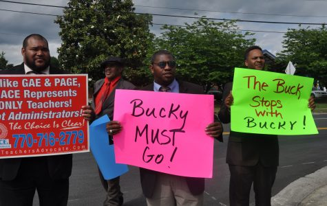 """Toting signs calling for the removal of NC's principal, Joseph """"Bucky"""" Horton, four men stood outside the school on Tuesday afternoon. Disclosing little more than their affiliation with the Metro Association of Classroom Educators, one protester explained, """"we can't really go into detail because of personnel issues."""""""