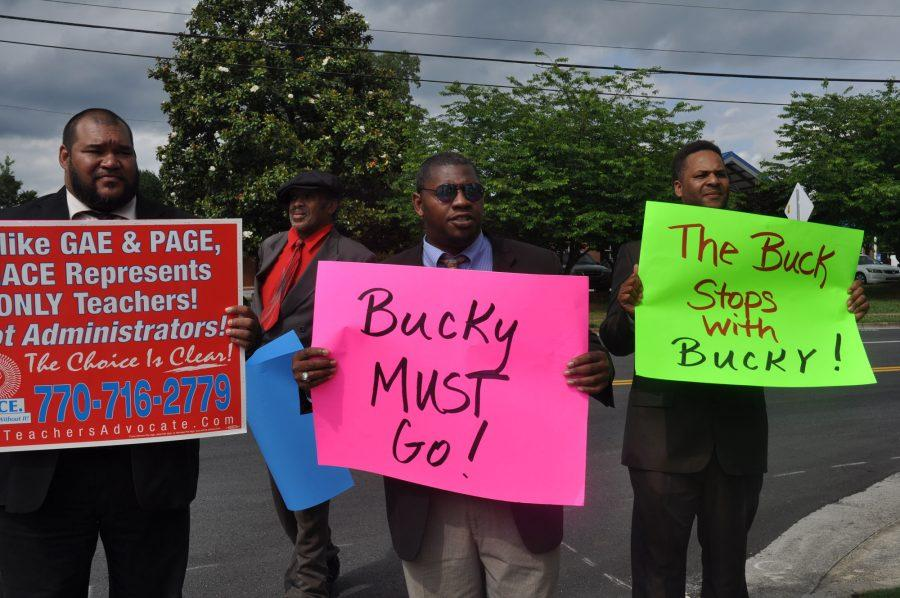 "Toting signs calling for the removal of NC's principal, Joseph ""Bucky"" Horton, four men stood outside the school on Tuesday afternoon. Disclosing little more than their affiliation with the Metro Association of Classroom Educators, one protester explained, ""we can't really go into detail because of personnel issues."""