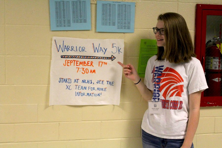 """Senior Cross Country member Audrey Widmier promotes the Warrior Way 5K, which will take place on Saturday, September 17 at 7:30 a.m. See any Cross Country runner or coach to fill out an entry form. """"We'd love for anyone to come out and run. Have fun, get fit,"""" Head Coach John Huff said."""
