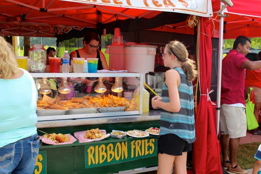 A citizen orders a tasty treat from one of the food vendors present at the City of Kennesaw's 16th Annual Pigs and Peaches festival.