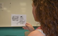 An NC student looks at an ad for the new After School Satan Club, run by The Satanic Temple.