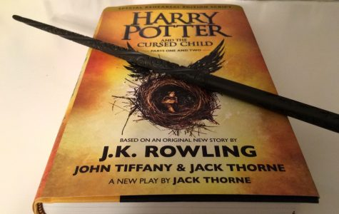 A student shows off the play Harry Potter and the Cursed Child, as well as a replica wand from the movie. The new piece, based on an original story by J.K. Rowling and written by Jack Thorne and John Tiffany, hit bookstores on July 31, 2016.