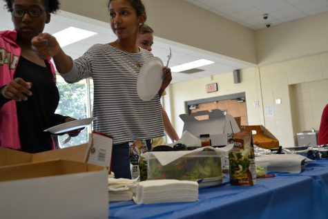"""Junior Claudia Checo passes plates to hungry magnet students. Checo gave a brief presentation to current sophomores about how to survive sophomore year.  """"Make sure you do your bundle homework the day it is assigned,"""" Checo warned."""