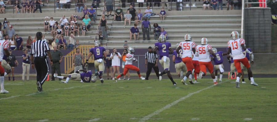 #12 Imad Strozier runs along the sidelines looking for room to run while getting blocks from multiple teammates.