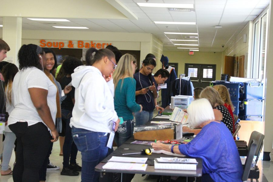 Seniors gather in the cafeteria to pick up their cap and gown orders, as well as their senior merchandise.