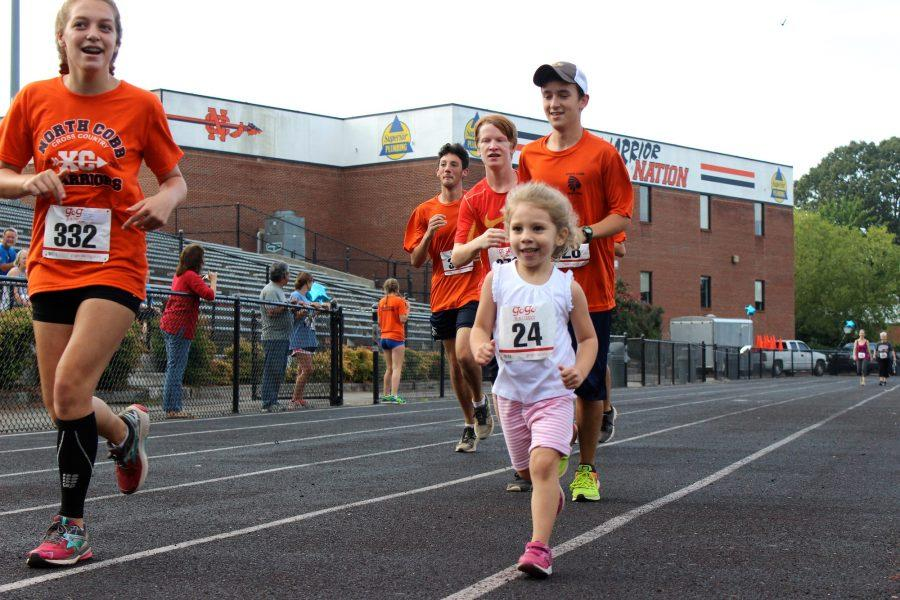 Members of the Cross Country team help a young racer cross the finish line of the 1K Fun Run.