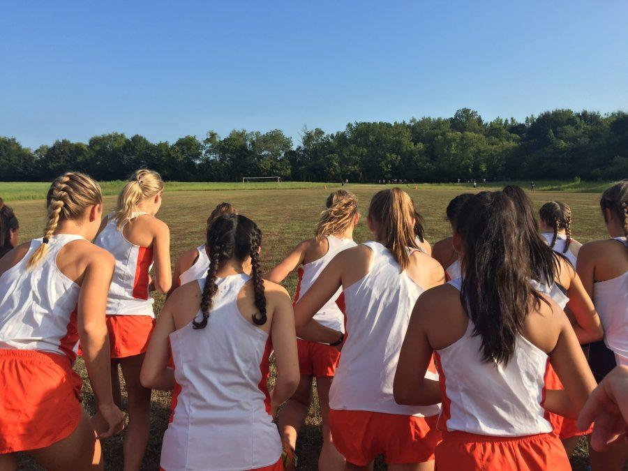 The Cross Country team's varsity girls warm up in unison before the race.