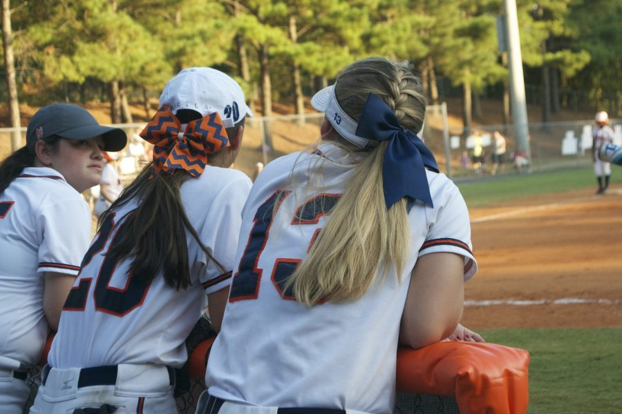 Seniors Mikila Mullen and Kendra Roach watch the game intensely from the dugout, while cheering on their teammates on the field.