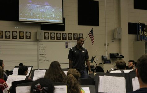 Frazier laughs and enjoys teaching band class as they watch footage of halftime performances.