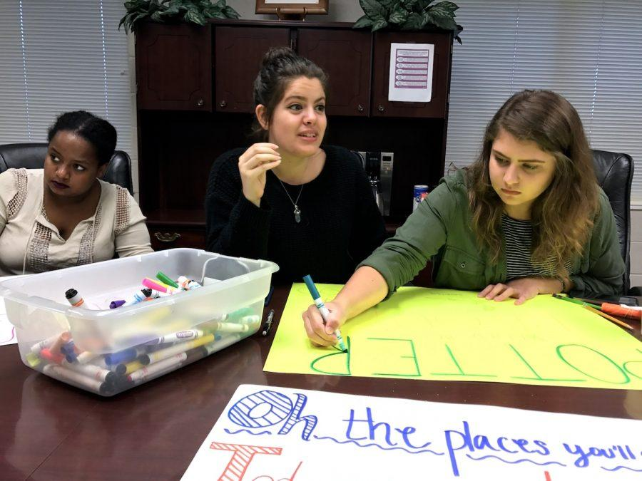 Seniors Bethel Mamo, Melissa Sagaseta, and Karsyn McCluskey design posters to cheer with at the event.