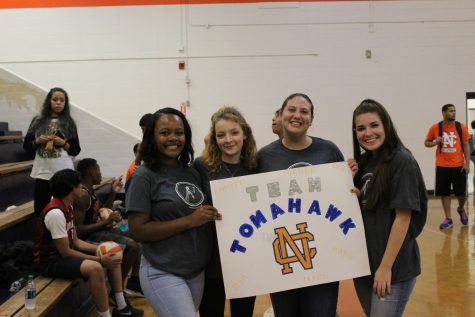 Excited fans Ashley Davis, Jules Shelly, Caroline Long, and Kallie Dever smile with posters to represent their team, Team Tomahawk.