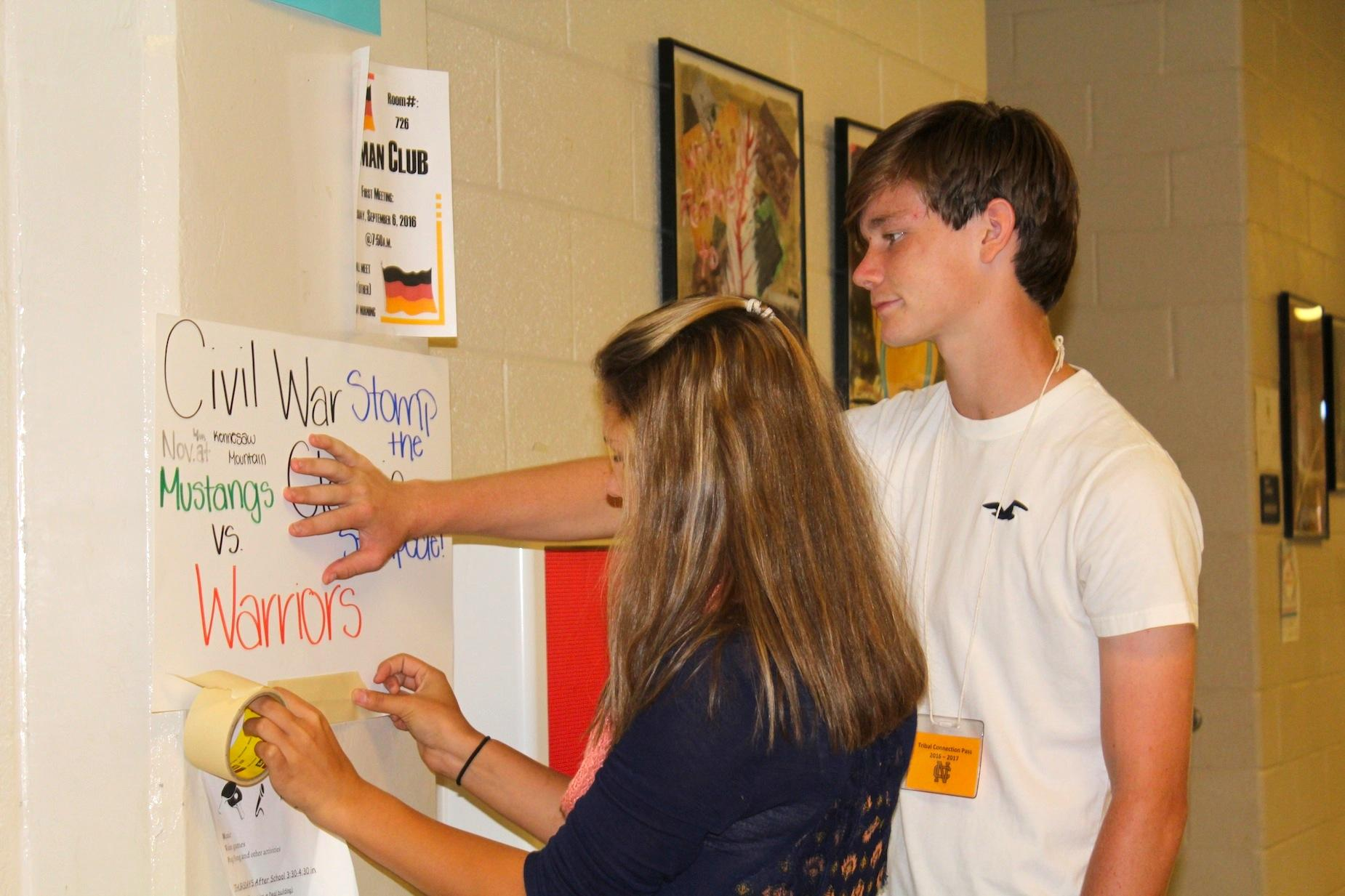 Freshmen Malina Cagle and Brian Morgan are hanging up posters promoting today's Civil War game against the Kennesaw Mountain Mustangs. The Warriors plan to continue their dominance against their in-town rival as they look for their eighth consecutive win. The game will be played at Kennesaw Mountain, so make sure to go out and support the Warriors!
