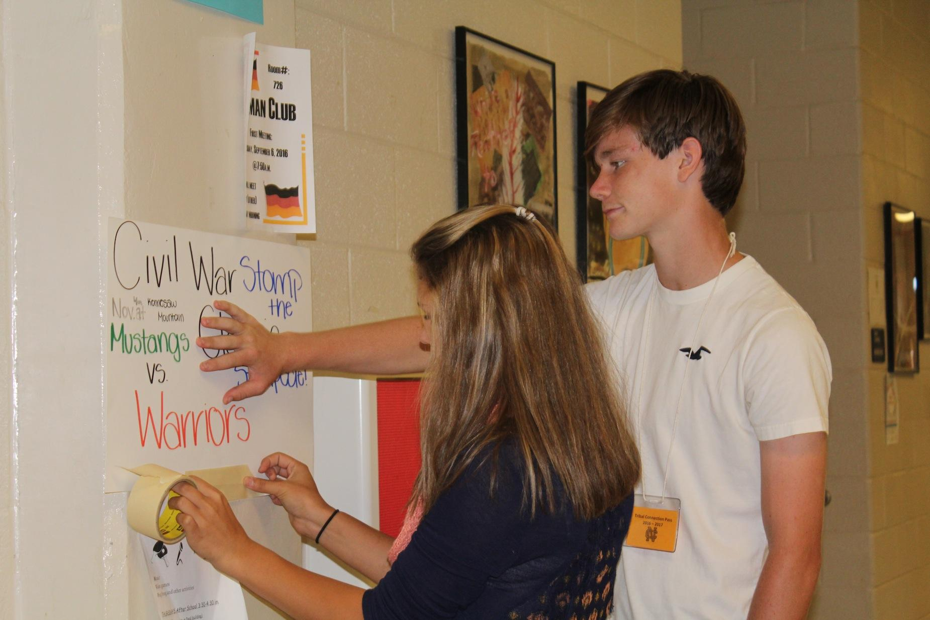 Freshmen Malina Cagle and Brian Morgan hang up posters promoting this Friday's Civil War themed game against the Kennesaw Mountain Mustangs. The Warriors plan to continue their dominance against their in-town rival, as they look for their eighth consecutive win against them. The game will be played at Kennesaw Mountain, so make sure to go out and support!