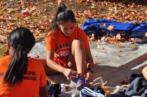 Junior Stefanie Garcia ties her spikes in preparation of the race