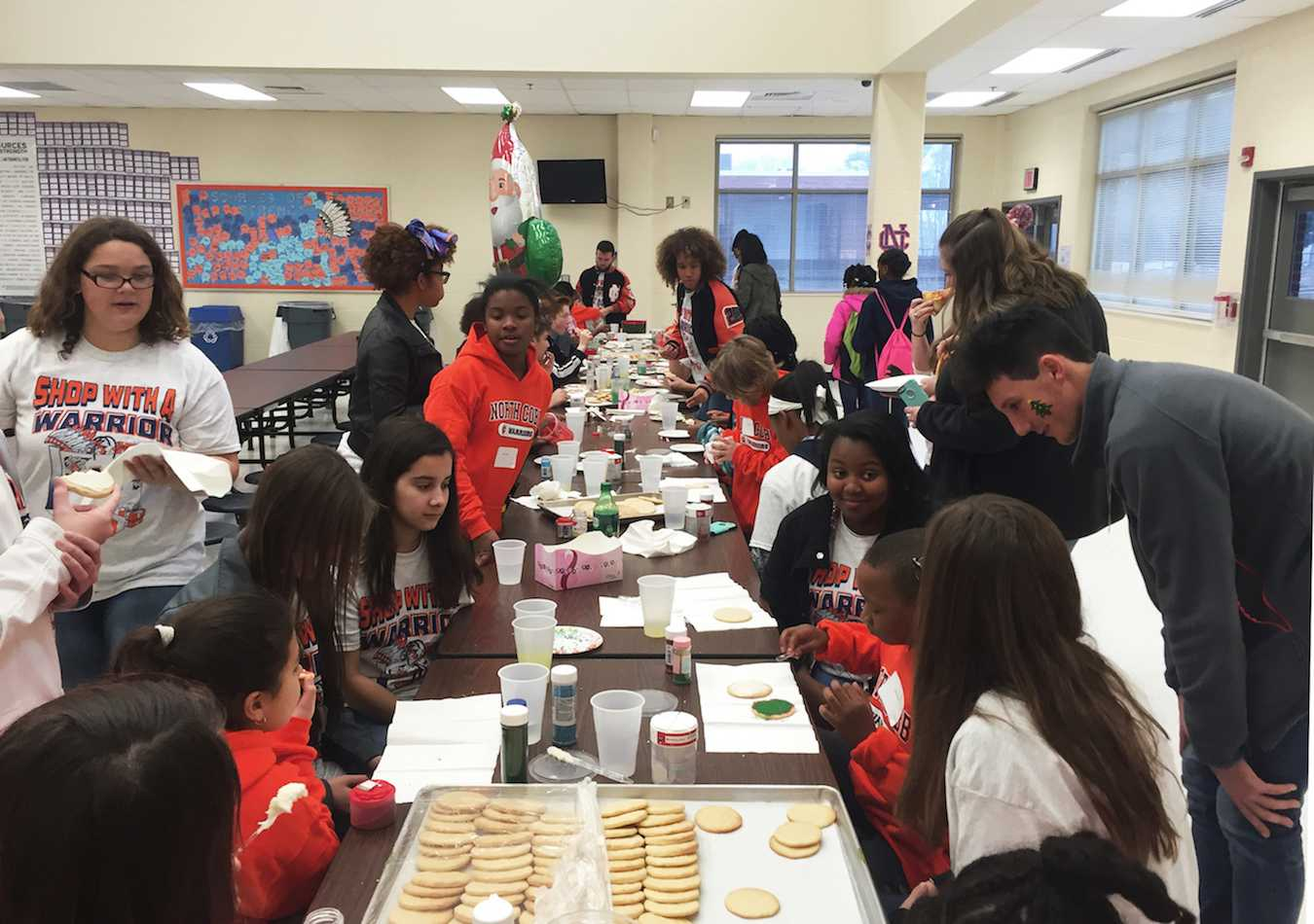 In the freshman cafeteria, little warriors decorate their own sugar cookies with Christmas colored icing and sprinkles.