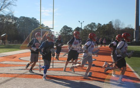 The varsity lacrosse team jogs around the field, conditioning and preparing for the upcoming season.