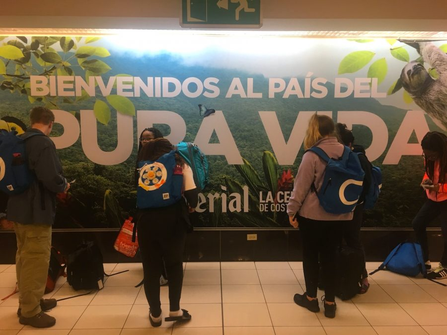 After landing in Alajuela, Costa Rica, students wait for the rest of the group stuck in passport check in front a sign with the national motto 'Pura Vida'.