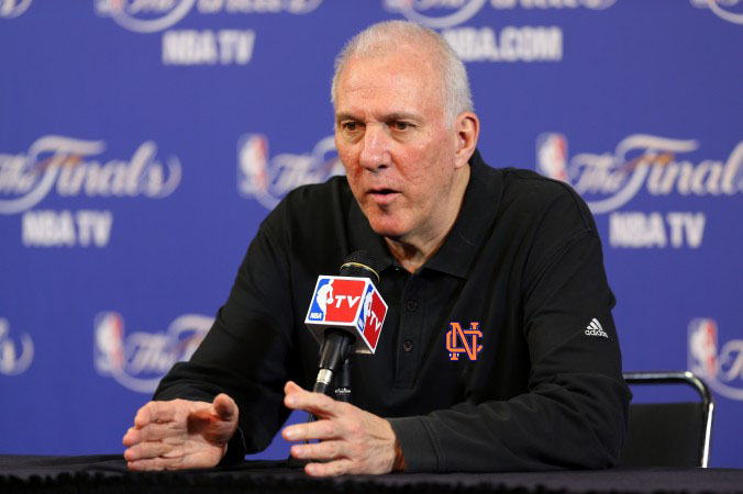 Popovich reveals in a press conference his new coaching job, wearing the NC logo
