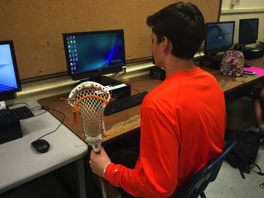 Sophomore and varsity lacrosse player Noah McKouen cradles his lacrosse stick in his left and types with his right, exhibiting his dedication to the game. The NC varsity lacrosse teams began the season strongly with two wins and one loss thanks to the dedication of the team's athletes.