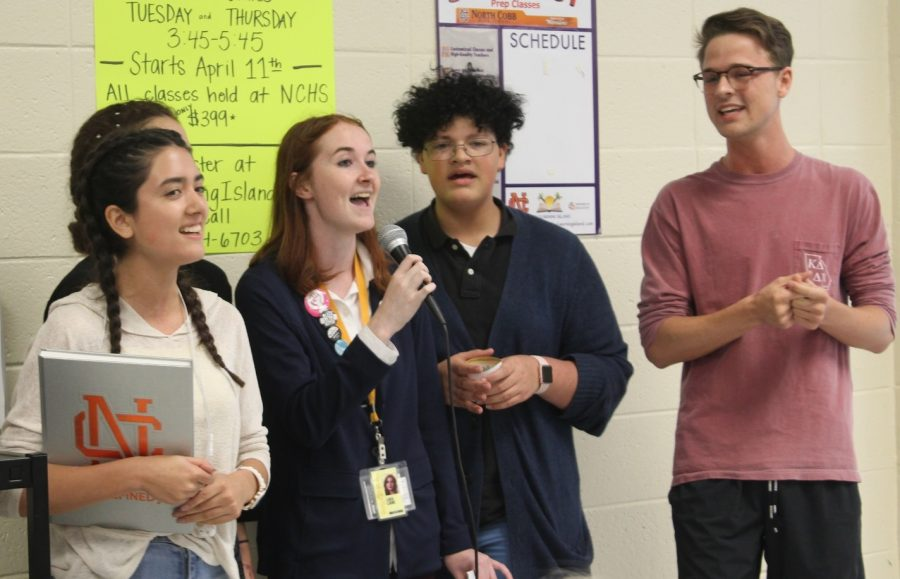 """Seniors Allie Fuentes and Kat Shambaugh, junior Jordan Hicks, sophomore Hope Kutsche, and freshman Deandre Mallory sing in the main cafeteria to preview the upcoming school musical, 25th Annual Putnam County Spelling Bee. The performances will take place on April 27, 28, and 29, and cast and crew members begin selling tickets this week for $10 each. """"For my first time acting, I'm thrilled to be performing a lead role in front of my peers, and I'm excited to be a part of such an amazing cast and crew,"""" Mallory said."""