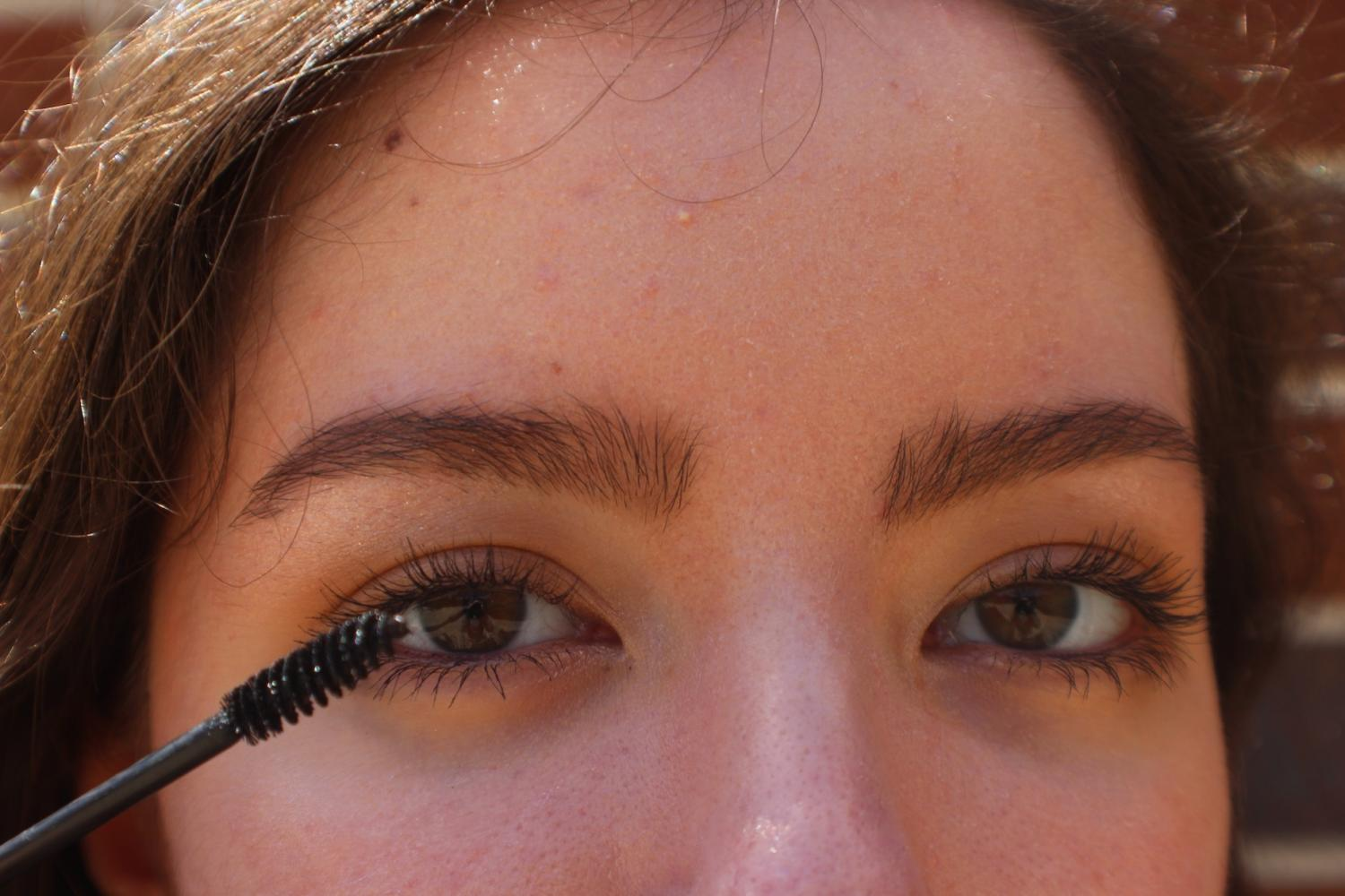 A student experiments with mascara, using the latest beauty trend.