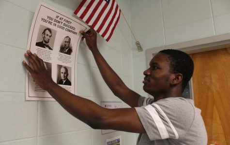 """Junior Godsgift Caleb helps AP U.S. History and Current Issues teacher Tamara Rankenburg remove wall decorations from her classroom in preparation for summer painting. """"Taking posters down changes how everything feels. It just feels empty and bare and boring,"""" Rankenburg said. """"But I'm fine taking it down as long as the wall gets painted."""""""
