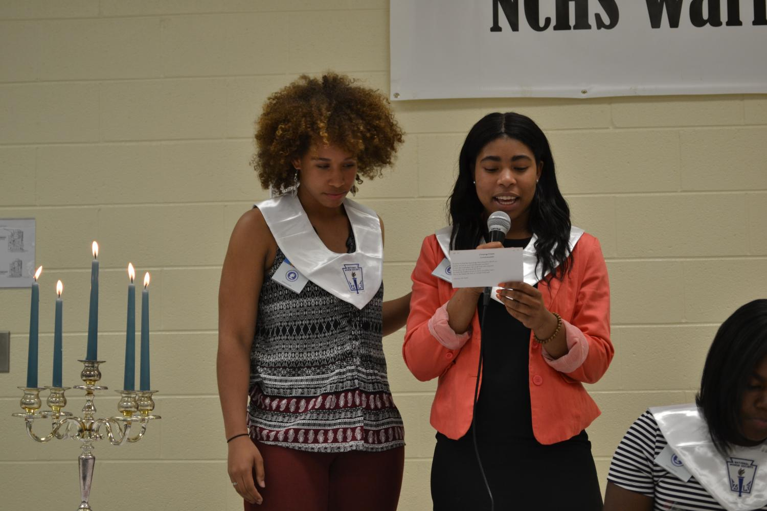 Seniors Celina Cotton and Erin Belmar read the closing poem, ending the induction ceremony.