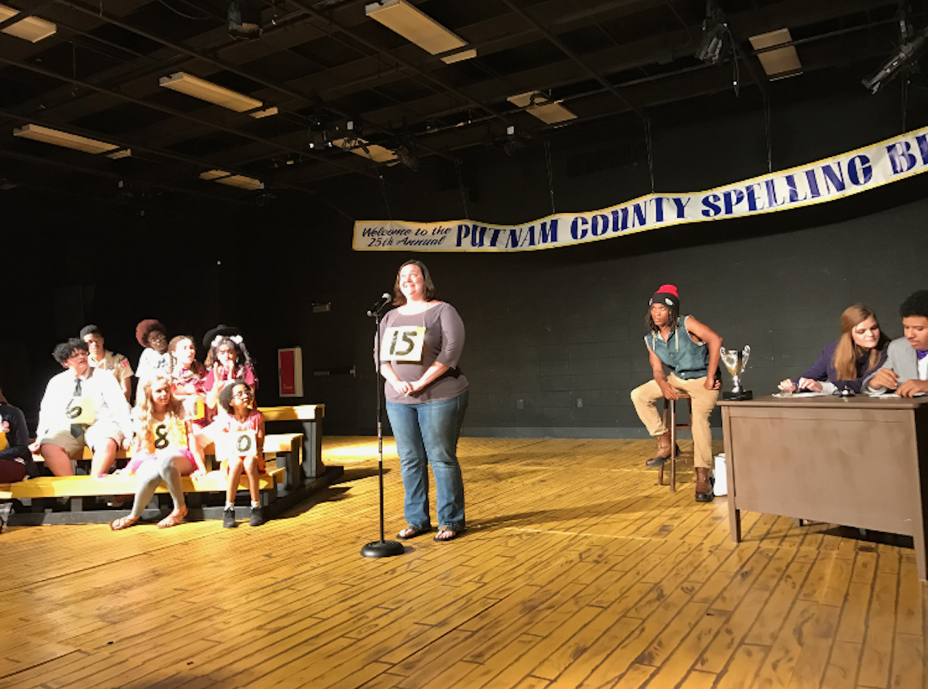 AP Comparative Government and AP Art History teacher Carolyn Galloway takes the stage as an audience volunteer for NC Standing Ovation's production of The 25th Annual Putnam County Spelling Bee. She took on the challenge of spelling complicated words and danced with the performers.
