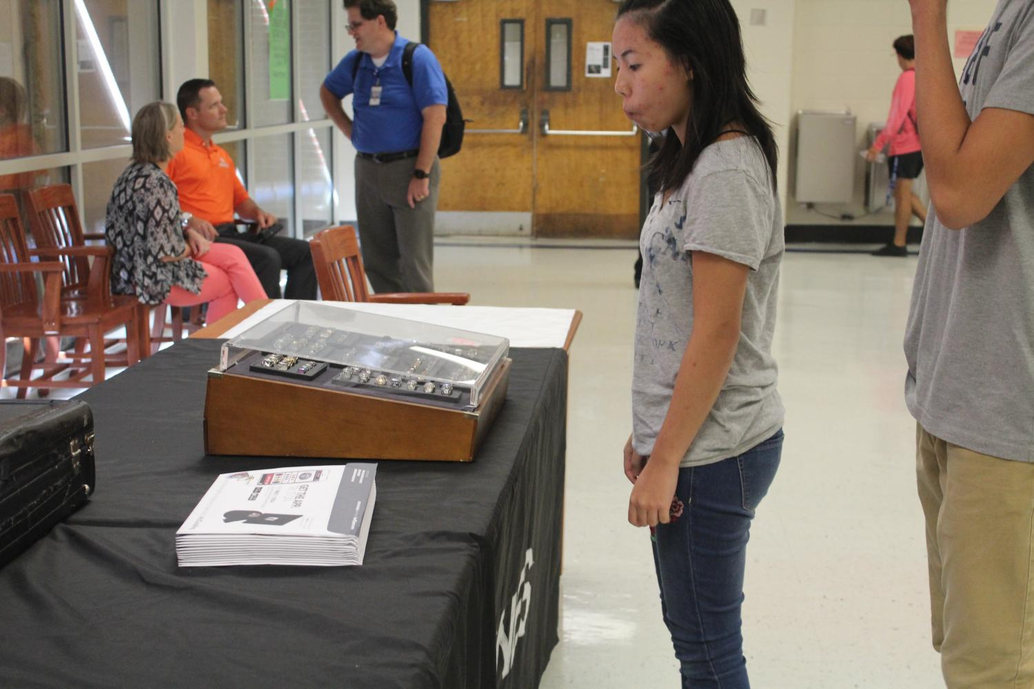 Herff Jones made an appearance in the cafeteria this week to promote class rings to the junior class. A student examining the ring case, which shows a variety of different rings for juniors and seniors. The display includes the sizes and different stones you can choose for your ring.