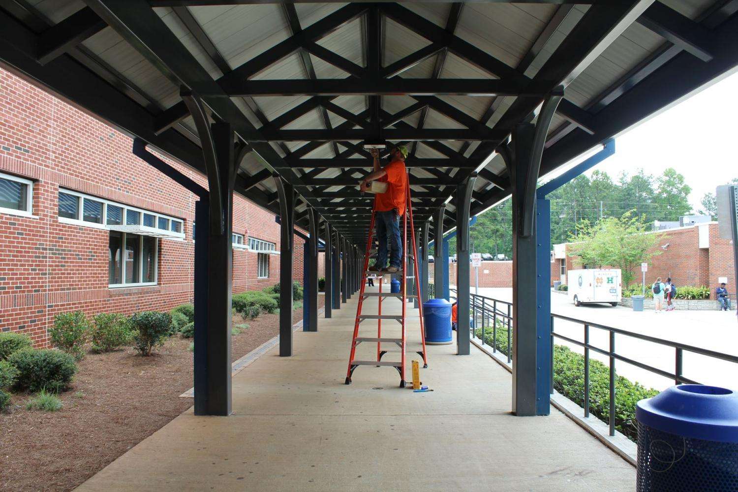 Construction+worker+Trey+Pruitt+replaces+light+bulbs+outside+entrance+of+freshman+academy.+As+he+works%2C+students+try+to+avoid+the+ladder+in+the+middle+of+the+hallway.+%E2%80%9CI+find+the+spot+a+bit+inconvenient%2C+but+at+least+they+are+getting+replaced%2C%E2%80%9D+said+NC+senior+Jordan+Hicks.