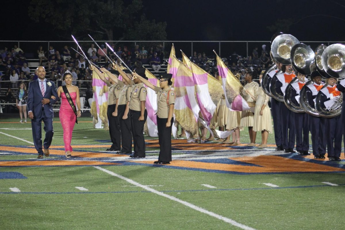 Tribal Connections organized the presentation of the homecoming court during halftime, featuring the band, color guard, and ROTC. Above, sophomore Madeline Hewitt struts across the field with her father during the ceremony. After the princesses lined up on the field, the crowd broke into applause as principal Bucky Horton and NC alumni Celina Cotton crowned senior Maya Hercey as queen.