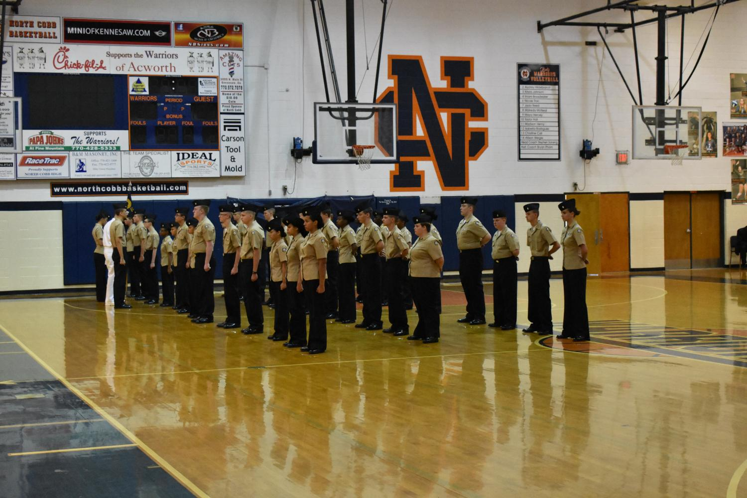 A portion of the NC unit stands at attention as they wait to receive a uniform inspection from the presiding officer. The NC band waits behind them to play during the unit's ceremony.